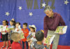 El autor del libro infantil James Luna entregando su libro a los estudiantes de la Escuela Primaria Carl Waitz, en Alton, Texas.